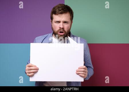 Serious man is holding a blank, white board, advertising space or announcement. - Stock Photo