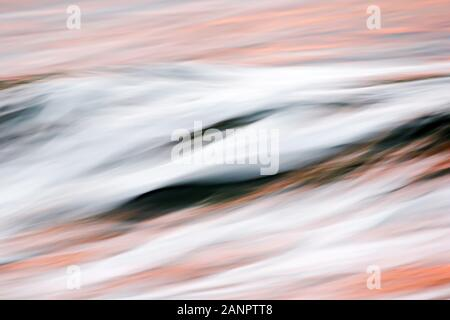 A blurred, muted wave showing reflections of a sunset in Costa Rica. - Stock Photo
