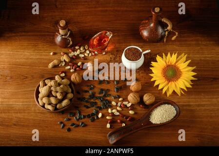 Vegetable oil in bottles, healthy seeds and nuts on old wooden floor - Stock Photo