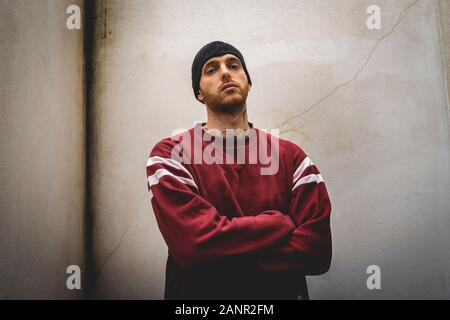 portrait of young rapper posing in front of a white wall in the suburbs - Stock Photo