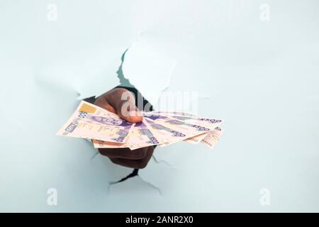hand of a black male person through a hole in a cardboard paper holding some money - Stock Photo