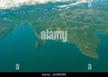 View from airplane window seat of Newfoundland land and Atlantic Ocean. - Stock Photo