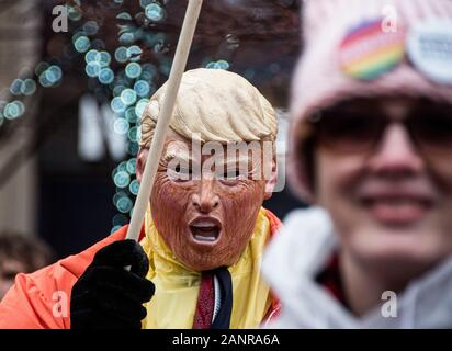 Dayton, USA. 18th Jan, 2020. A protester wearing a mask representing U.S. President Donald Trump stands in the crowd during the march.Women's March is an annual event that is held across the USA every year to honour women's rights. There were marches in many cities across our country this afternoon, and they were attended by women's rights activists, politicians, and citizens, alike Credit: SOPA Images Limited/Alamy Live News - Stock Photo
