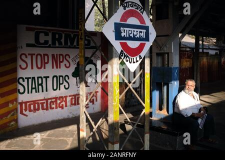 A commuter sitting on the platform of Byculla Station in Mumbai, India, waiting for his train into the suburbs