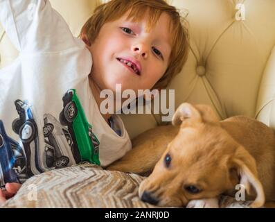 Little blonde boy playing with his puppy on couch - Stock Photo
