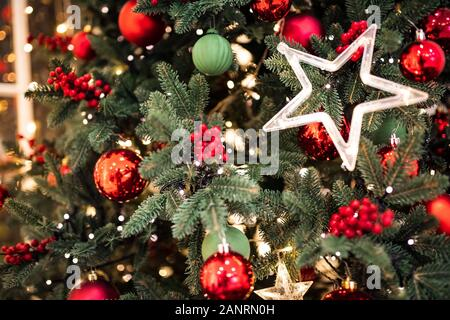 Christmas pine tree branch with decorations red balls gifts and star