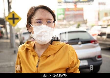 Woman wearing face mask protect filter against air pollution (PM2.5) or wear N95 mask. protect pollution, anti smog and viruses, Air pollution caused - Stock Photo
