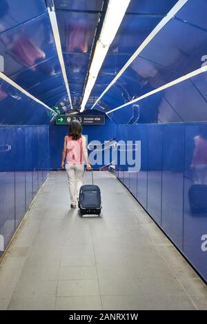 Woman with her suitcase walking through a train station tunnel. Concept of travel - Stock Photo