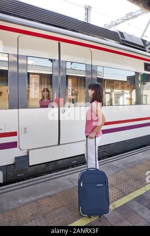 Traveler woman walking and waits train on railway platform. Concept of travel - Stock Photo