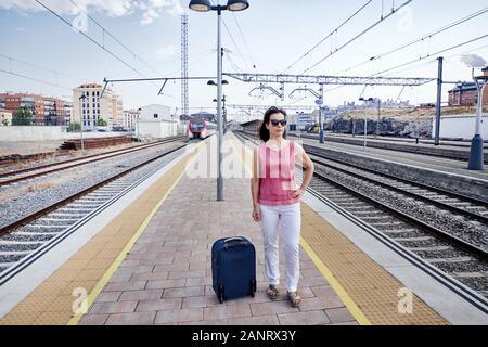 Traveler woman walking and waits train on railway platform. Concept of travel - Stock Photo