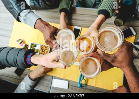 Group of friends enjoying a beer glasses in english pub restaurant - Young people cheering at vintage bar - Friendship, happy hour and party concept -