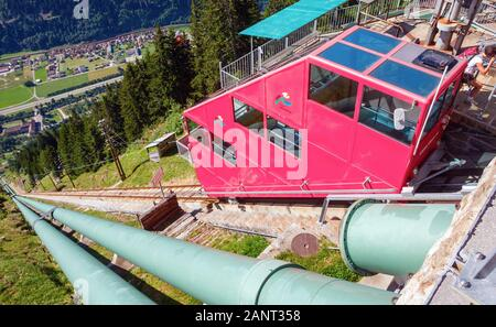 View of the Piora Valley with the village Piotta, looking down the Ritom funicular railway on a sunny day. Switzerland. - Stock Photo