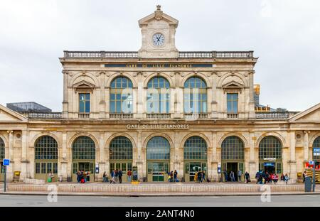 PLACE DE LA GARE, LILLE, FRANCE - APRIL 15, 2017: Frontal view of Lille Flandres railway station (Gare de Lille Flandres) under a cloudy sky. It is a - Stock Photo