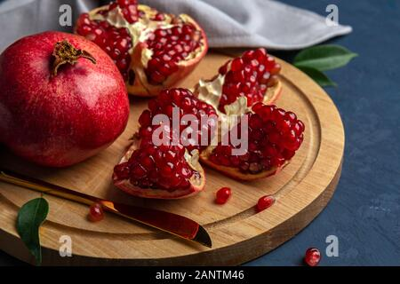 Pieces of pomegranates on a cutting board with a knife on a dark blue background. Close-up, horizontal orientation. Stock Photo