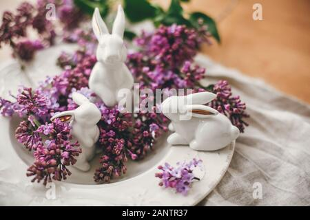 Stylish Easter white bunnies on vintage plate and lilac flowers on rural fabric. Ceramic rabbits decorations and spring flowers. Space for text. Holid