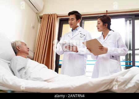two young friendly asian doctors talking to senior asian male patient at bedside in hospital - Stock Photo