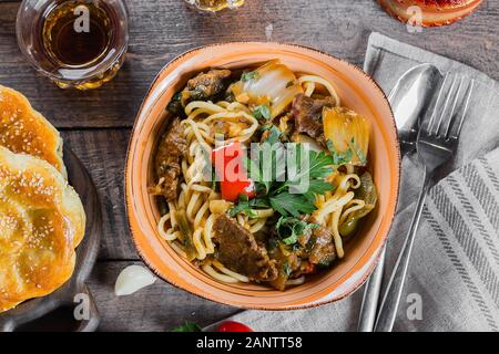 Traditional asian uzbek noodle lagman with vegetables and meat on rustic wooden table background. Top view - Stock Photo
