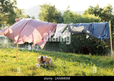 Pink and blue bedding sheet on forest background under the bright warm sun. Clean bed sheet hanging on clothesline at backyard. Hygiene sleeping ware concept. - Stock Photo