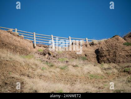 A view from below of the loss of land due to coastal erosion on the cliff face at Saunton Sands Beach in North Devon, England, UK. - Stock Photo