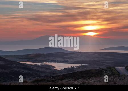 From Dalry Moor Road near Fairlie are the Arran Mountains as the sun goes down behind the island. A naturaly hazy image due to the weather and the sun - Stock Photo