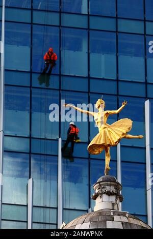 Statue of Russian ballerina Anna Pavlova on top of the dome of Victoria Palace Theatre and workers on glass fronted building, Victoria, London, UK - Stock Photo