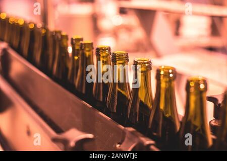 View of glass bottles on the conveyor belt, bottle necks on the production line, brewery equipment, inside wine factory, process of alcohol liquor man - Stock Photo