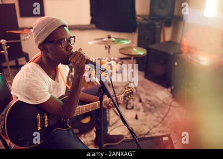 High angle portrait of contemporary African-American man singing to microphone and playing guitar during rehearsal or concert with music band in recording studio, copy space
