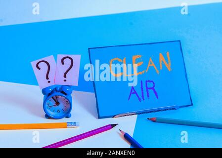 Writing note showing Clean Air. Business concept for air that has no harmful levels of dirt and chemicals in it Mini size alarm clock beside stationar - Stock Photo