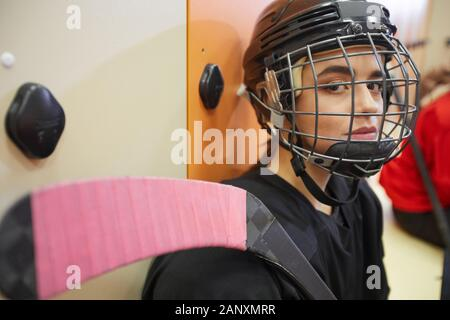 Closeup portrait of beautiful young woman wearing hockey gear and looking at camera while posing in locker room, copy space - Stock Photo
