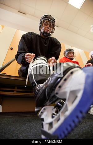 Low angle view at female hockey player putting on gear in locker room while preparing for match or practice, copy space - Stock Photo