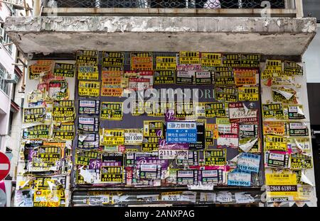 A recently closed handbag shop front is plastered with estate agent advertisements. Businesses in Hong Kong suffer regularly being forced to shut as l - Stock Photo