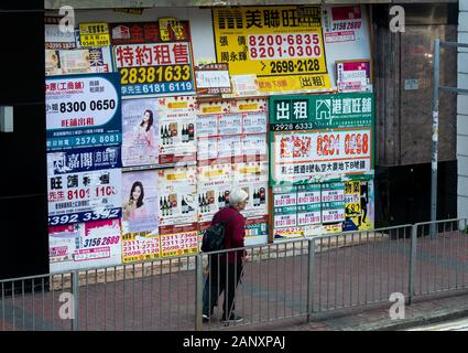A recently closed shop front is plastered with estate agent advertisements in Wan Chai Hong Kong. Businesses in Hong Kong suffer regularly being force - Stock Photo