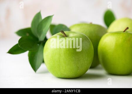 Green apples with green leaf on white table closeup view. Healthy crispy fresh fruits - Stock Photo