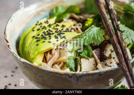 Buckwheat noodles soba with tofu, broccoli, avocado, seedlings and cilantro. Healthy vegan food concept.
