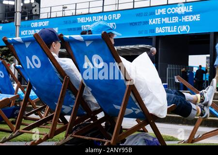 Melbourne, Australia. 20th Jan, 2020. Tennis: Grand Slam, Australian Open. Spectators sit in rain ponchos on the tournament grounds. Heavy rain and thunderstorms have swept over parts of the fire zones in south-east Australia. Credit: Frank Molter/dpa/Alamy Live News - Stock Photo