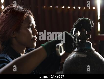 Female apprentice industrial engineer, inspecting and maintaining compressed gas cylinders in production plant - Trainee student intern, learning on the job skills during work experience - Stock Photo