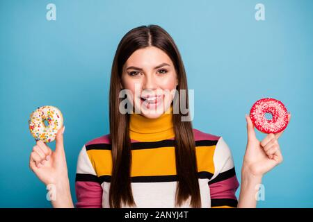 Close up photo of funky positive emotions girl hold two pastry sugary cookies lick lips want eat wear casual style jumper isolated over blue color - Stock Photo