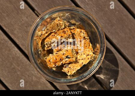 A glass jar filled with homemade rusks on a wooden surface - Stock Photo