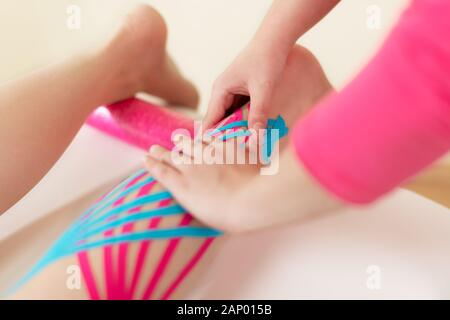 Physical therapist applying kinesio tape on female patient's calf. Kinesiology, physical therapy, rehabilitation concept. Close up. - Stock Photo
