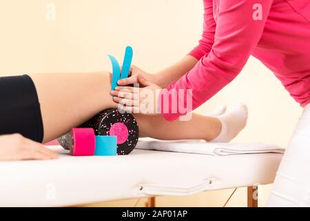Physical therapist applying kinesio tape on female patient's knee. Close up cropped shot. Kinesiology, physical therapy, rehabilitation concept. - Stock Photo