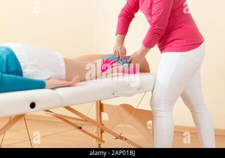 Physical therapist applying kinesio tape on female patient's leg. Kinesiology, physical therapy, rehabilitation concept. - Stock Photo