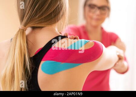 Young female patient wearing kinesio tape on her shoulder exercising with a professional physical therapist. Kinesiology, physical therapy, rehabilita - Stock Photo