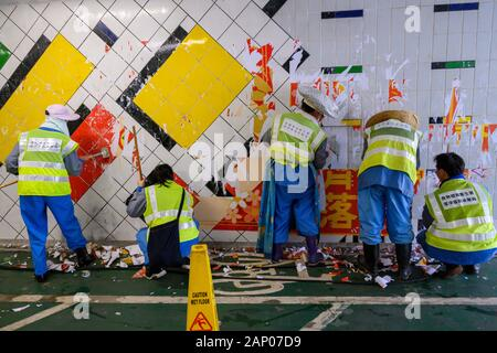 January 20 2020 Hong Kong.  Cleaners removing_anti_government_posters_from a Lennon _Wall_ in_Hang_Kou_Tsuen_Kwan_O. - Stock Photo