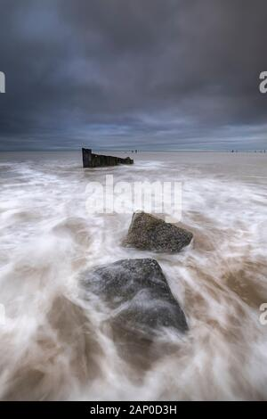 Broken sea defences on the Norfolk coast at Happisburgh. - Stock Photo