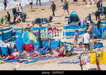 Holidaymakers enjoying themselves on Fistral Beach in Newquay in Cornwall. - Stock Photo