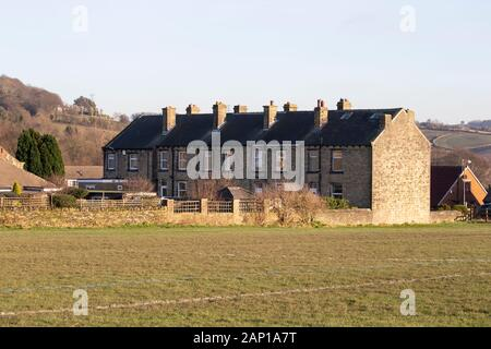 A series of typical Yorkshire stone built terraced houses with chimneys adjacent to a grass field in Huddersfield, West Yorkshire, U.K. - Stock Photo