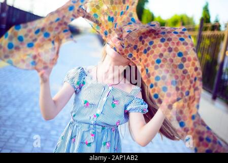 Portrait of a beautiful little girl in a dress playing with a fashionable scarf, tossing him in the air, and catches. - Stock Photo