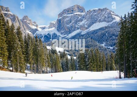 Skiers going down the slope at Sella Ronda ski route in Italy - Stock Photo