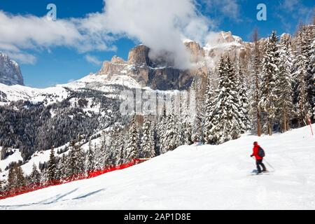 Skier going down the slope at Sella Ronda ski route in Italy - Stock Photo