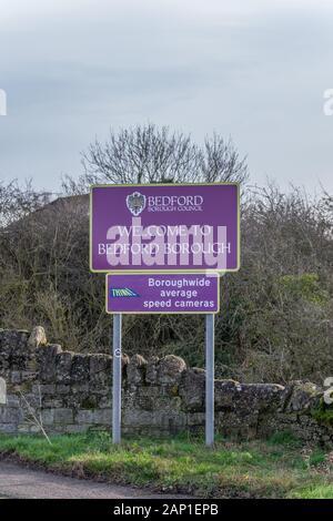 Roadside sign, Wecome To Bedford Borough and boroughwide average speed cameras; Turvey, Bedfordshire, UK - Stock Photo